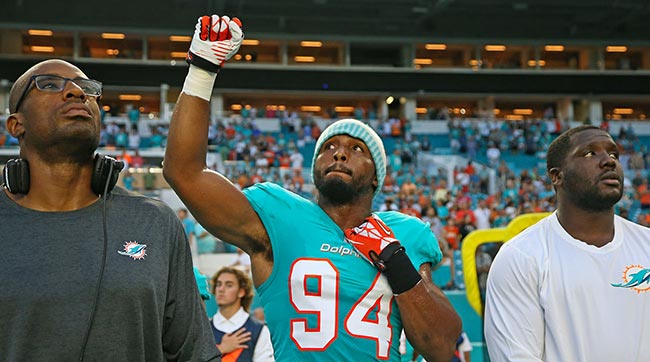 Robert Quinn raising his fist in protest during the anthem.